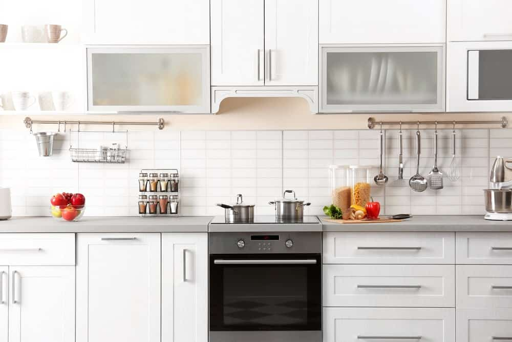 This is a close-up view of the white cooking area that has a hint of pinkish beige above the white tiles of the backsplash. The countertop of this kitchen peninsula is of a light gray hue that matches the oven stove as well as the drawer and cabinet fixtures.
