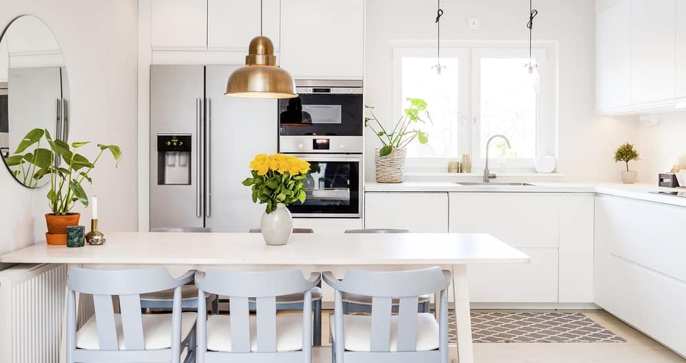 The brass pendant light hanging over the informal dining area catches the attention against the white built-in cabinets and drawers with handle-less designs for that solid white palette across the surfaces extending to the white countertop of the L-shaped kitchen peninsula.