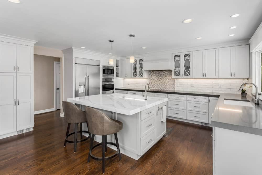 The hardwood flooring of this white kitchen is a good counterbalance for the brightness of the ceiling, cabinets, and drawers. This is mediated by the gray and metallic hues of the appliances, faucets, and fixtures.