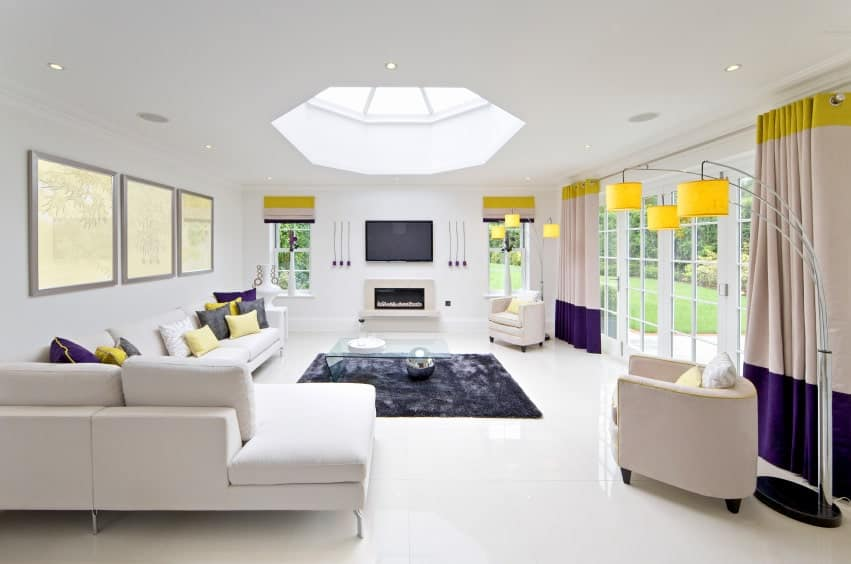 White living room featuring yellow and purple accents. It has a ceiling with a skylight, along with a fireplace with a TV on top of it.