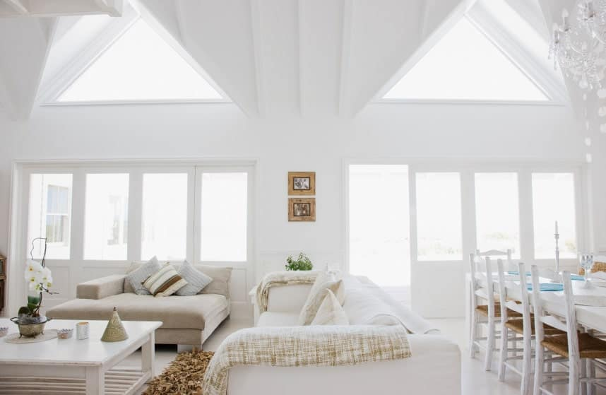 A great room with white walls and ceiling. Space offers a comfy set of seats along with a dining table set on the side.