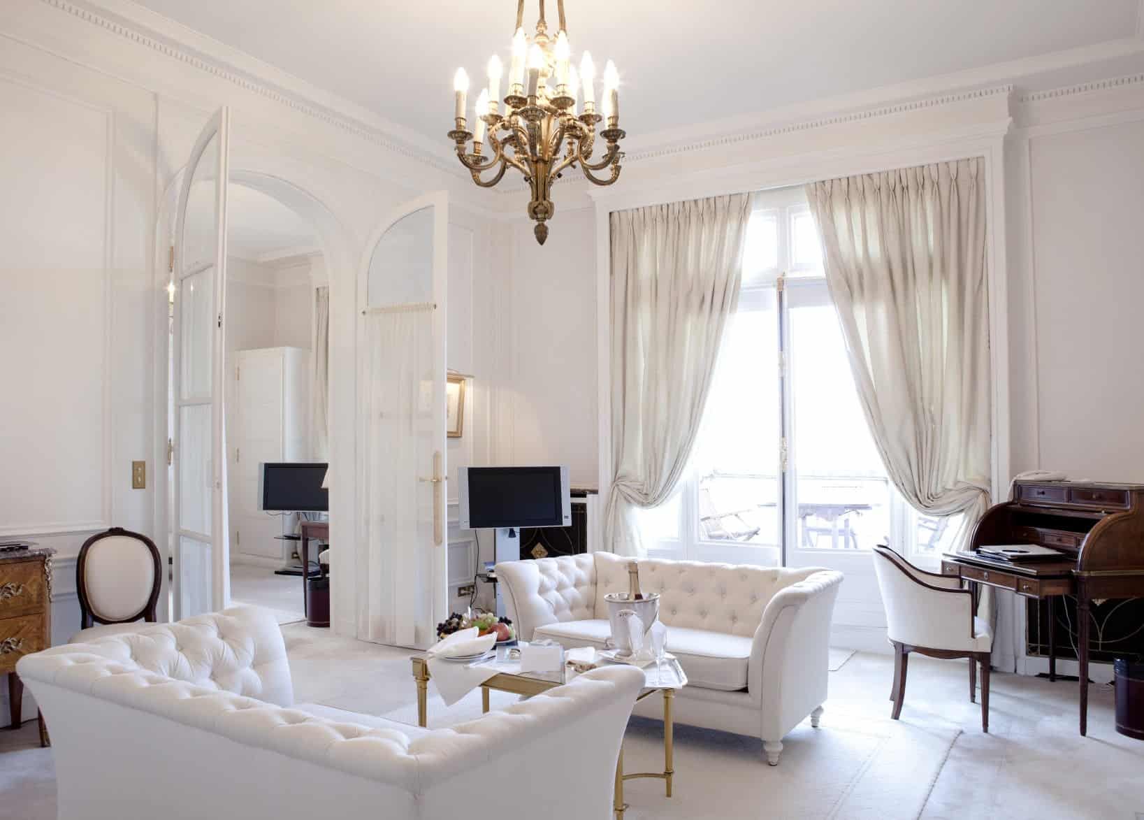 This living room features white classy couches and a nice center table. The room is lighted by a gorgeous chandelier.