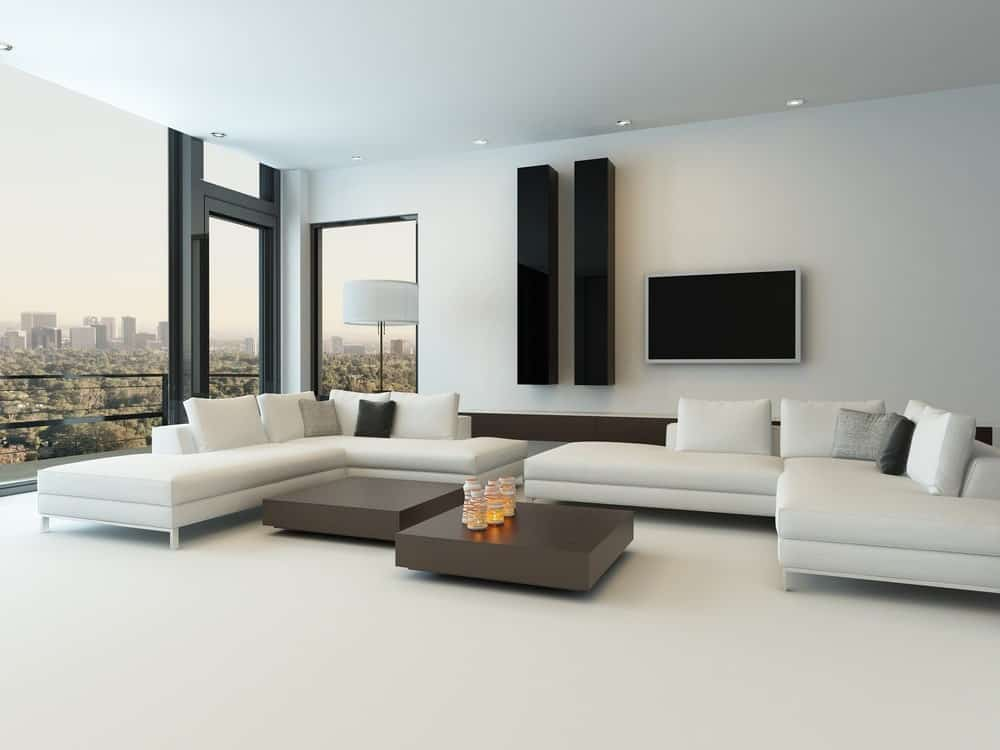 Large contemporary living room featuring white L-shape couches on the white flooring. The center tables look absolutely stylish. There's a TV on the wall as well.