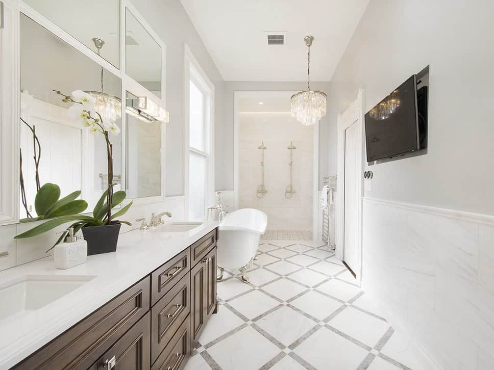 White master bathroom featuring two sinks and a freestanding tub, along with an open shower and a widescreen TV on the wall.