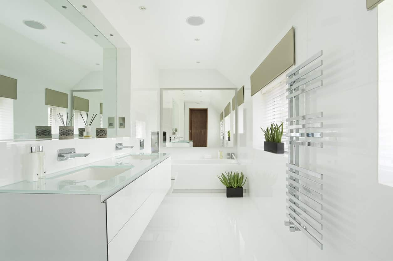 A modish master bathroom featuring a glass sink countertop with two sinks. There's a drop-in tub in the corner. There's a pair of potted plants as well, giving additional color to this white-themed bathroom.