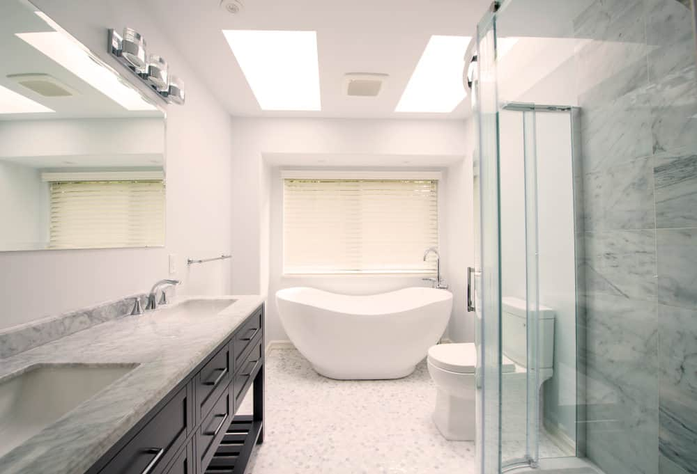 This master bathroom boasts a double sink with a marble countertop. There's a freestanding tub as well, placed under the two skylights.