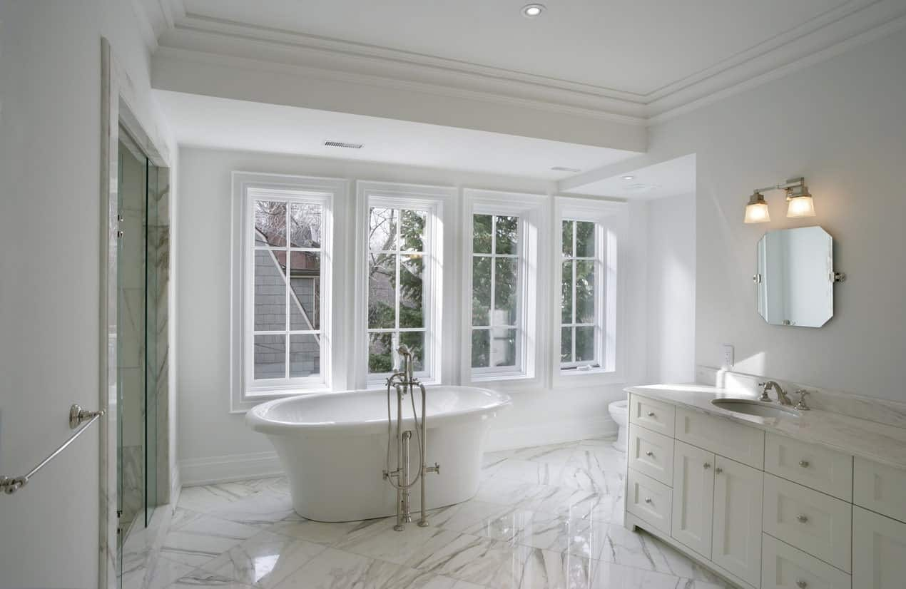 White master bathroom boasting beautiful marble tiles flooring. The room offers a freestanding tub and a walk-in shower room.