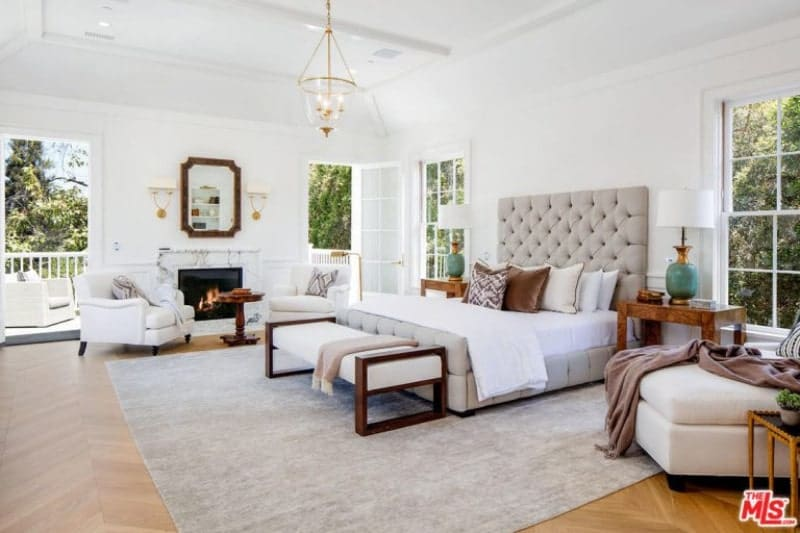 Spacious master bedroom featuring white walls and hardwood flooring topped by a gray area rug. It features a cozy bed setup along with a fireplace with two chairs nearby.
