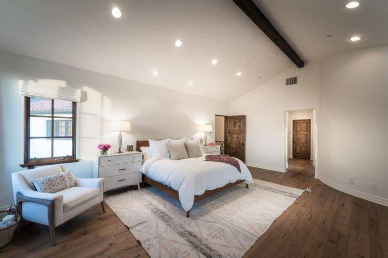 Minimalist master bedroom featuring white walls and rustic hardwood flooring. The room is lighted by recessed lights and table lamps.