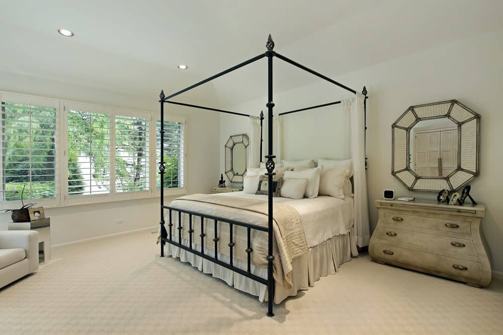 Master bedroom featuring white walls and white carpet flooring. The room offers rustic side tables and a chair on the side.