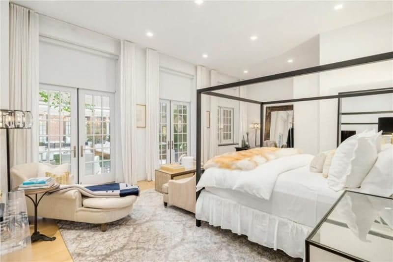 White master bedroom with a large area rug and multiple chairs. There are doorways leading to the outdoor area.