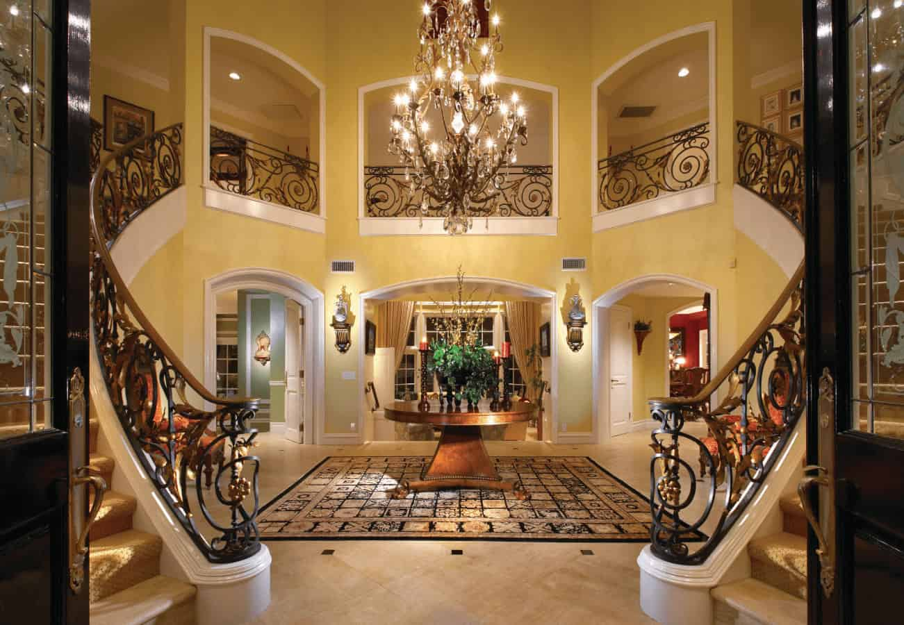 Elegant foyer showcases a round center table and upholstered chairs wrapped with a bifurcated staircase that's framed with ornate wrought iron railings.