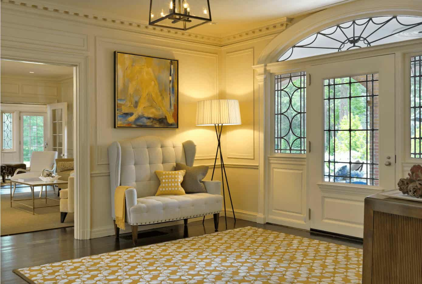Transitional foyer with glass windows and front door along with hardwood flooring topped by a yellow floral rug. There's a tufted wingback chair in the corner lighted by a floor lamp and caged pendant.