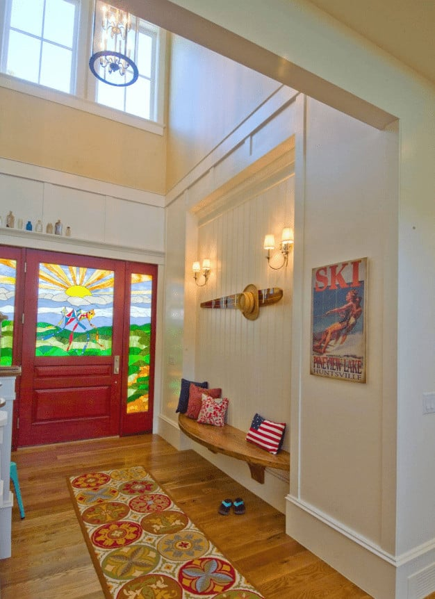 Yellow foyer accented with a redwood front door that's fitted with landscape stained glass. It includes an inset beadboard wall fixed with a curved bench that's topped with fluffy pillows and illuminated by a pair of sconces.