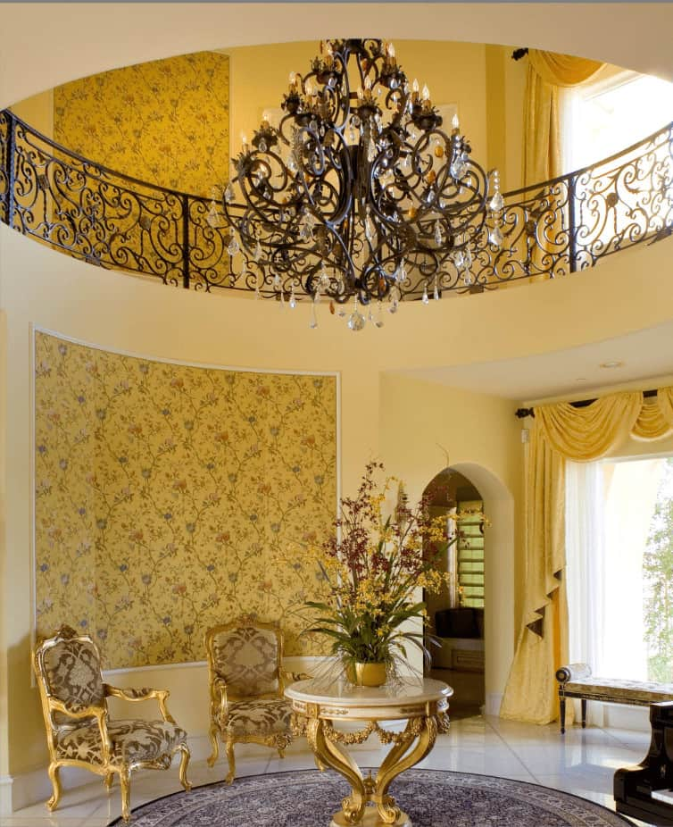 Fabulous foyer illuminated by a fancy chandelier and accented with a charming floral wallpaper. It has a gold center table paired with matching patterned armchairs.