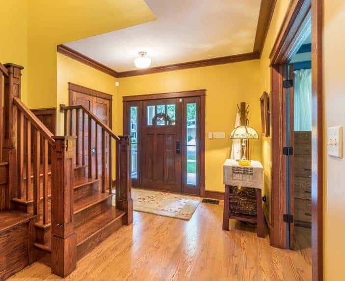 Traditional foyer with a wooden front door that complements with the crown molding and the staircase. It has a console table accompanied by a coat rack, mirror and a fancy table lamp.