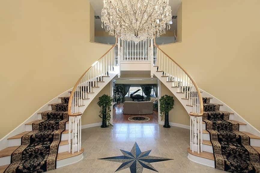 A grand foyer offers a light wood bifurcated staircase wrapped in classy black stair runners and lighted by an elegant chandelier.