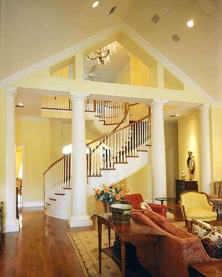 This home boasts a yellow foyer framed with white columns and filled with a wooden console table and winding staircase.
