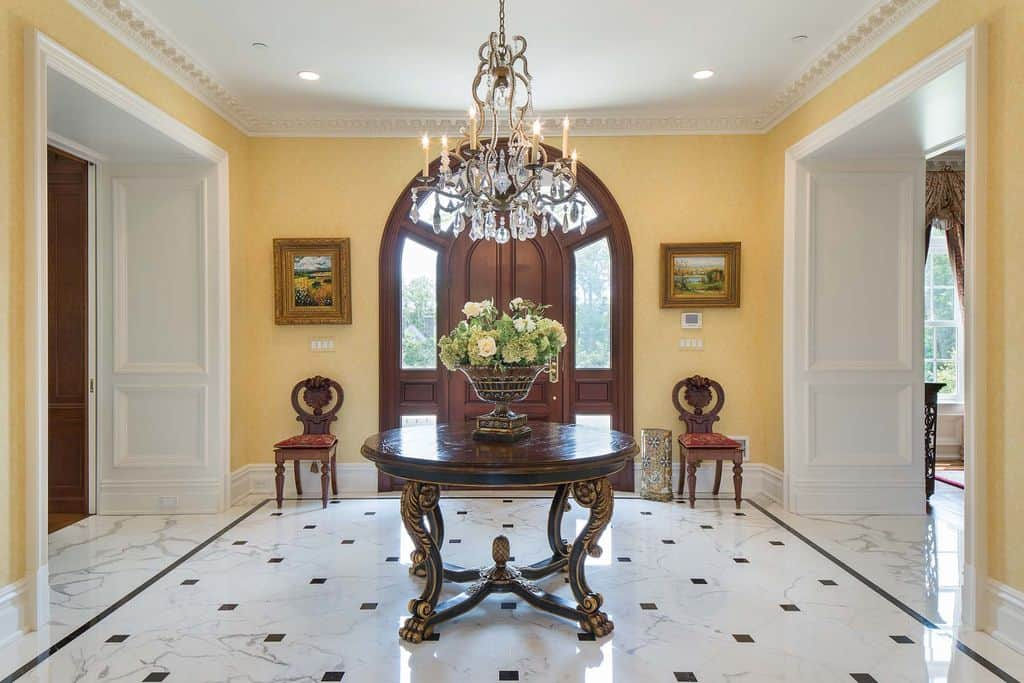 Symmetrical foyer with the round center table and crystal chandelier as the focal point. It has an arched door that sits in the middle of framed wall arts and wooden round back chairs.