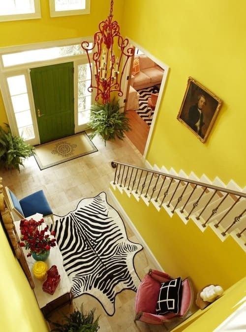 Bright yellow foyer decorated with an ornate red pendant and lovely portrait mounted above the staircase. It has a green entry door and limestone flooring topped by a zebra rug.