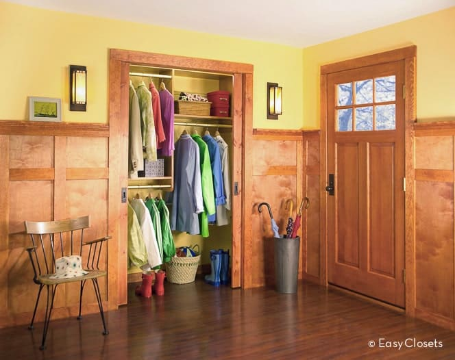 Yellow foyer with an open closet illuminated by wall sconces that are mounted above the wood paneling. It includes a wooden chair and umbrella rack beside the wooden front door.