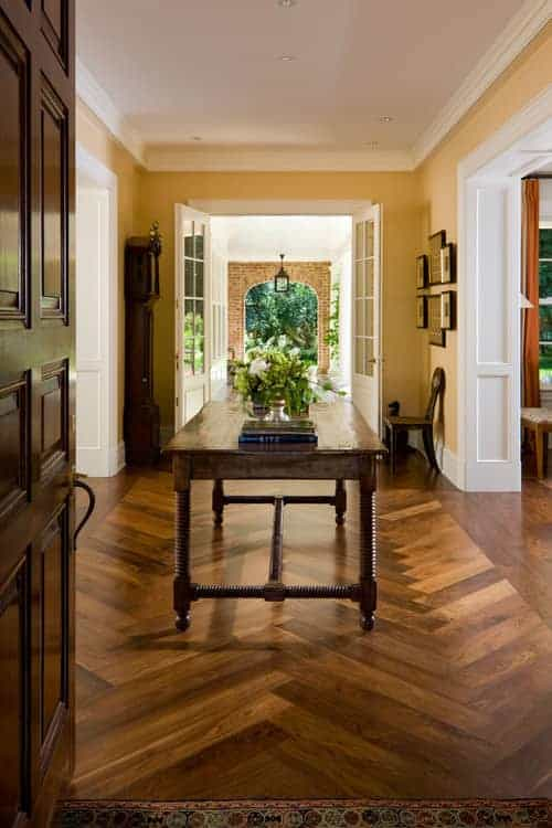 Cozy foyer with a wooden front door and center table that sits on herringbone wood flooring. There's a french door at the far end that opens to a stone brick archway.