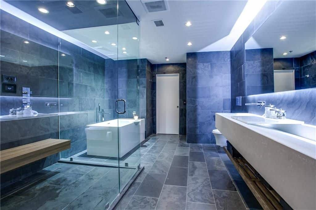 Spacious master bathroom boasts stylish gray flooring and blue walls. It also offers a freestanding tub, a shower room and a floating vanity sink.