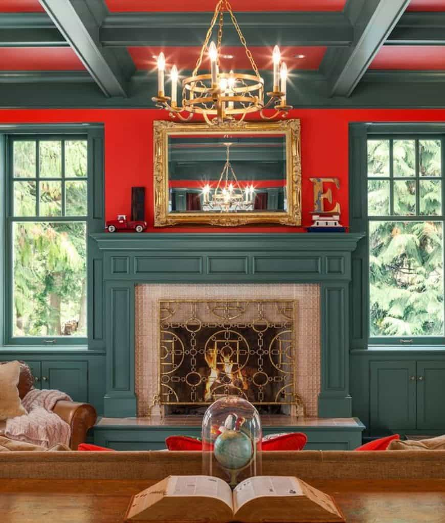 Farmhouse living room with a touch of elegance from the brass chandelier, gold framed mirror and ornate screen covering the fireplace framed with green mantel. Red walls and ceiling add a nice striking contrast which makes the room livelier.