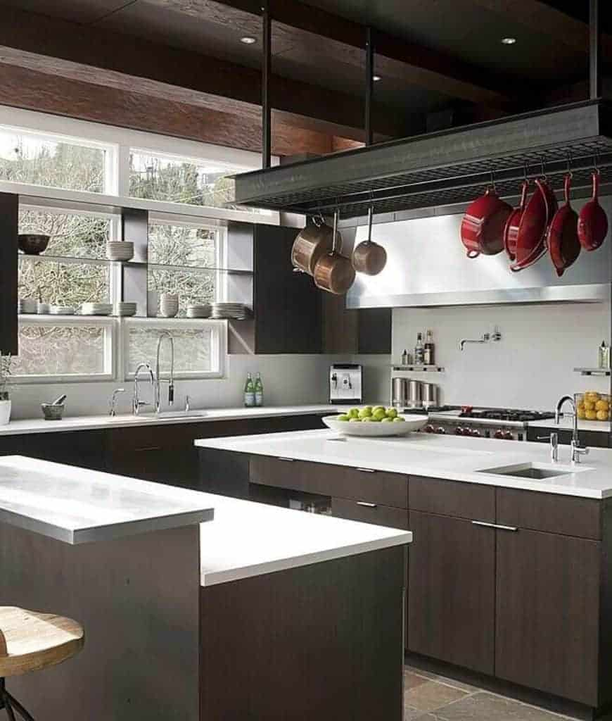 Modern kitchen boasting an immense metal pot rack with hanging brown and red pots is suspended over the dark wood kitchen island across the two-tier breakfast counter.