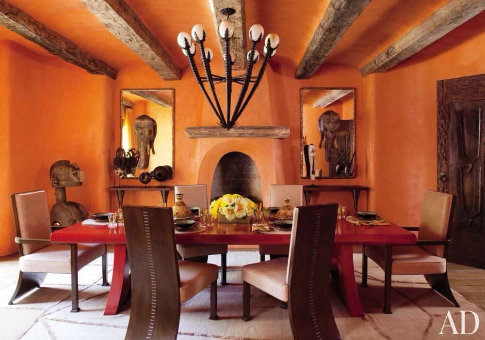Orange dining room with a large and attractive red rectangular dining table lighted by a handsome ceiling lighting situated on the orange ceiling with wooden beams.