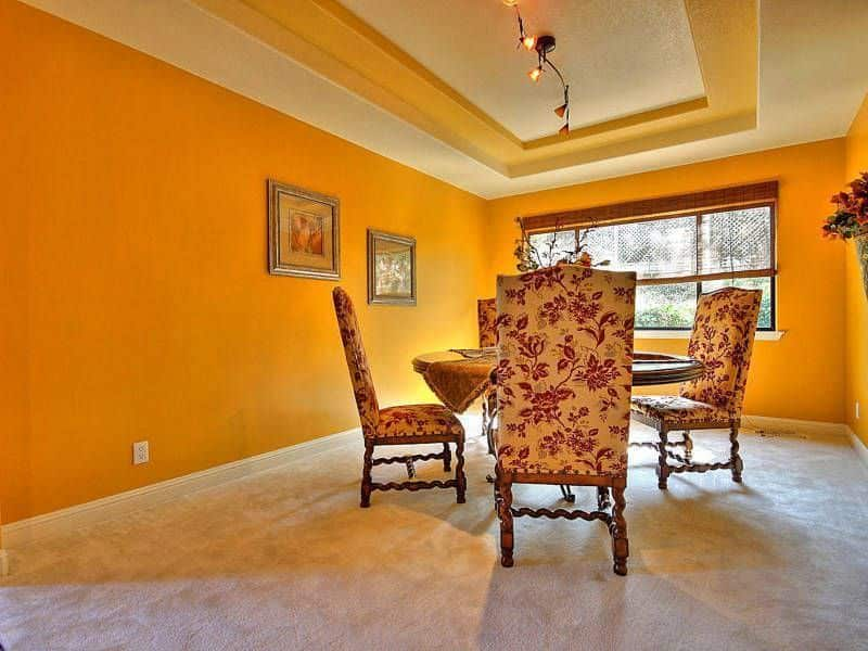 A dining space with a beautiful round dining table and chairs set. The area is surrounded by orange walls, along with carpet flooring and a tray ceiling.