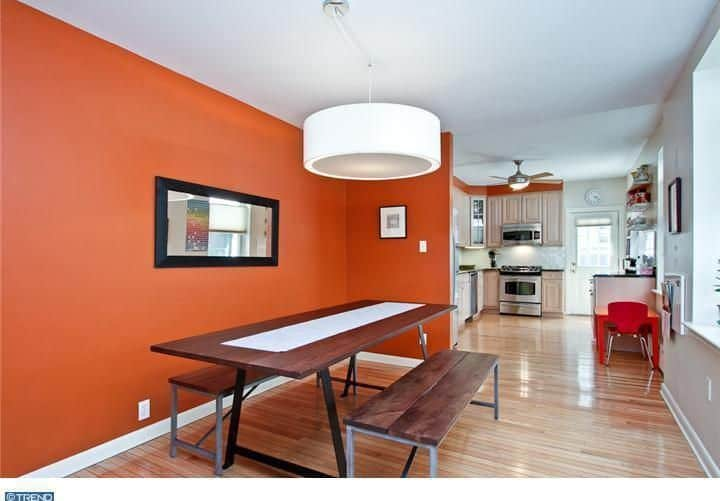 A dining space with hardwood flooring and orange walls, lighted by a large ceiling lighting.