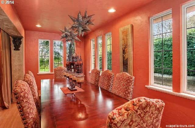 A dining room with orange walls and ceiling, along with orange dining table and orange chairs set.