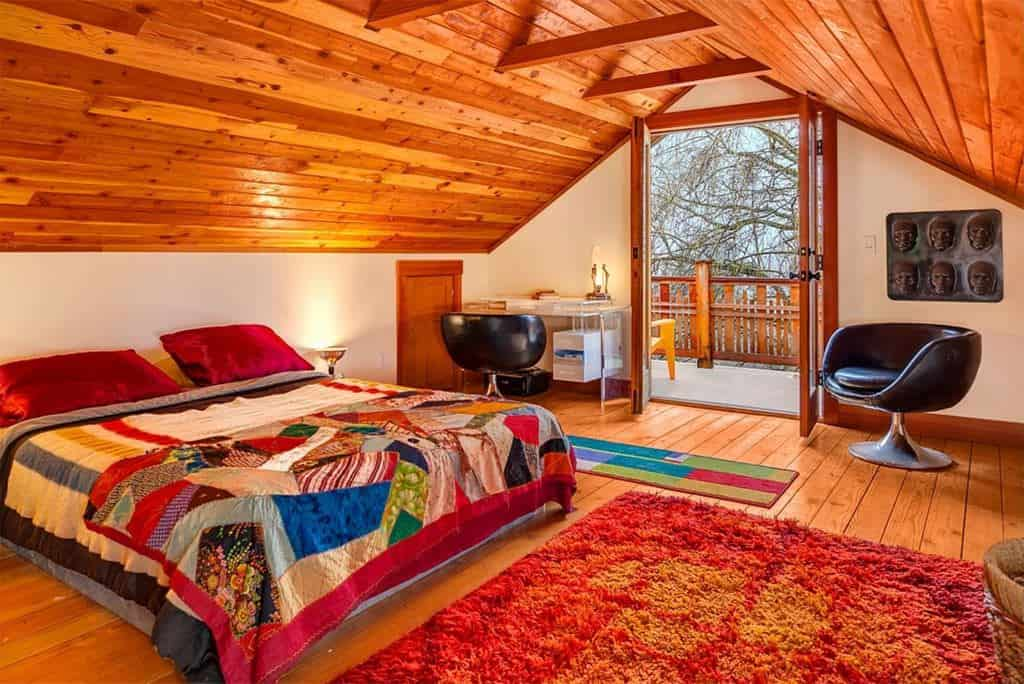 This primary bedroom featuring hardwood flooring matching the wooden vaulted ceiling. The room also has a doorway leading to the home's balcony.