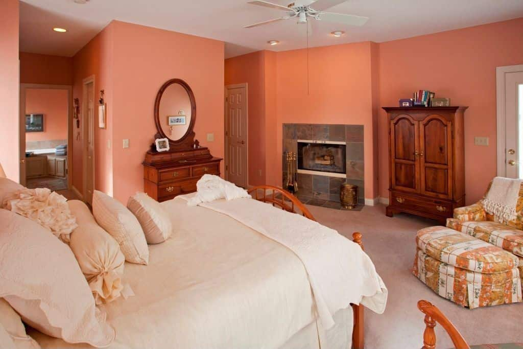 An orange primary bedroom with a cozy bed and a fireplace. It also has its own bathroom.