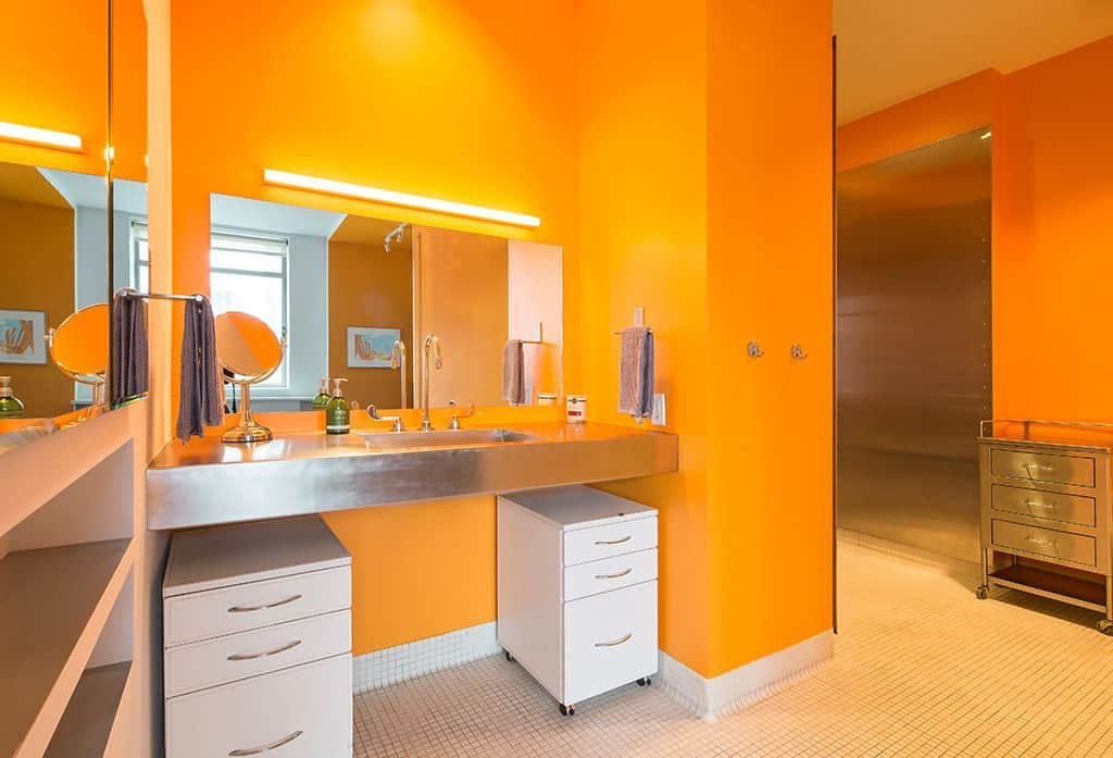 A primary bathroom with orange walls and white micro tiles floors. It has a floating vanity with a single sink.