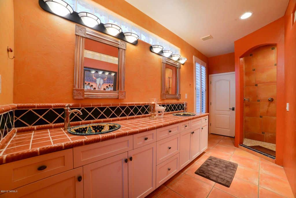 Orange primary bathroom with a stylish sink counter. The two sinks look very attractive. The room also offers a walk-in shower.