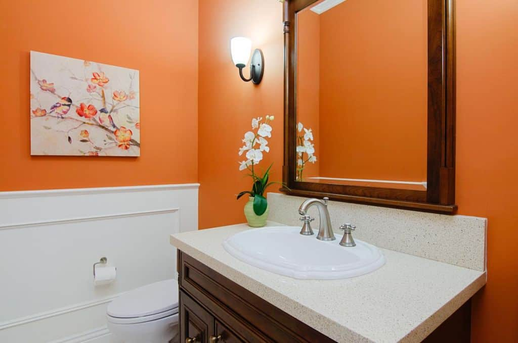 A close up look at this primary bathroom's white sink that looks perfect together with the orange accent.