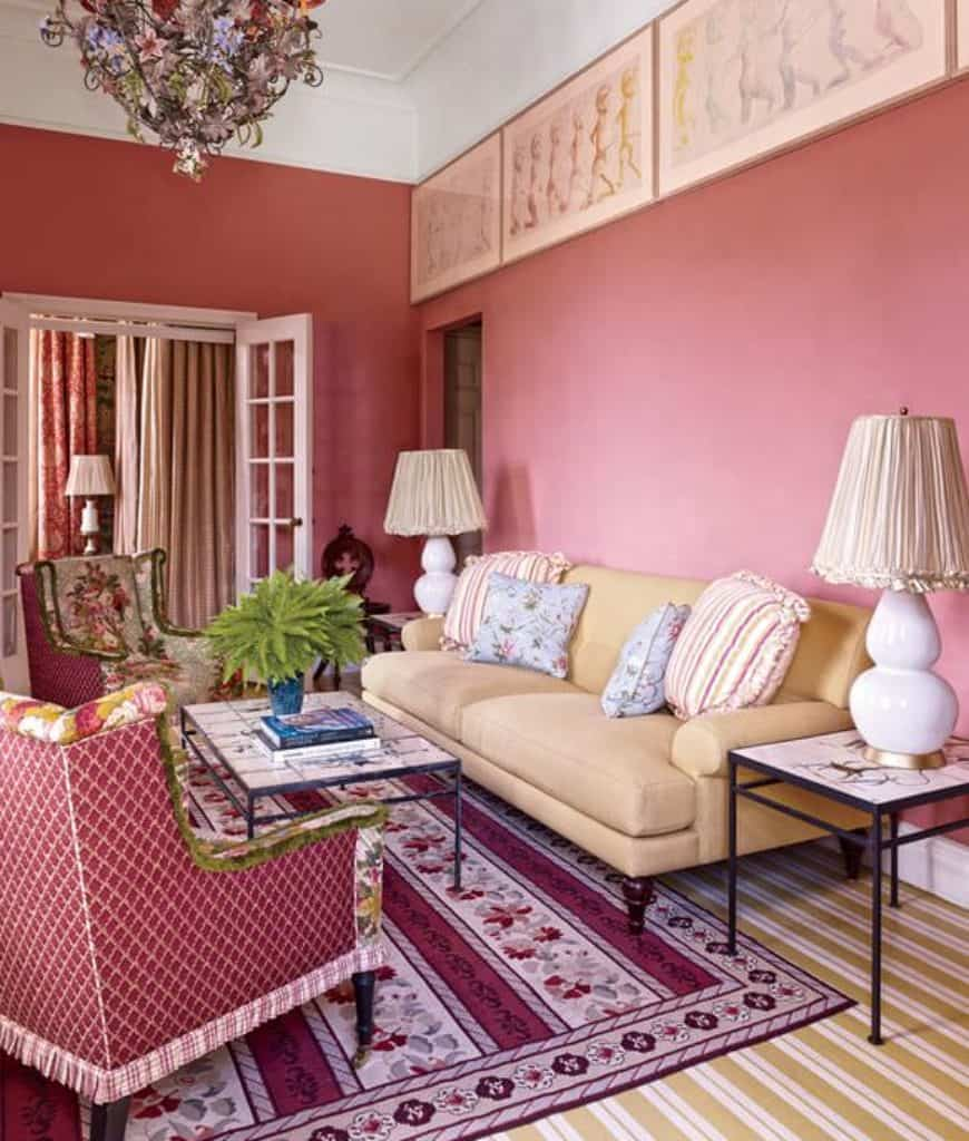 Charming living room decorated with a floral chandelier and framed wall arts mounted on the pink wall. It has a French door and yellow striped carpet flooring topped by a shabby chic rug.
