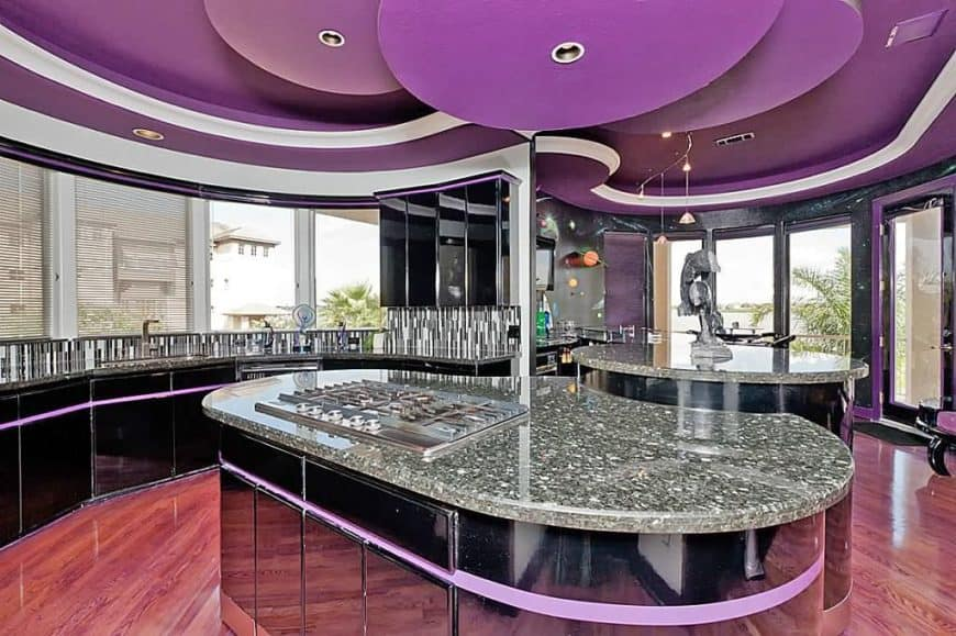 A stunning kitchen featuring two handsome islands, both with granite countertops. The purple and black accent look so good together.