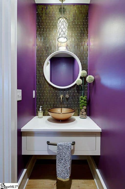 A focused look at this bathroom's floating vanity with a gold-finished vessel sink surrounded by purple walls.