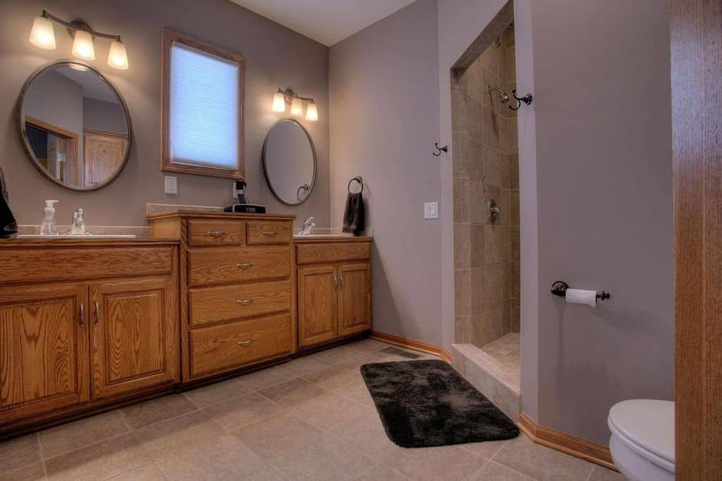 Spacious primary bathroom featuring purple walls and two sink counters, along with a walk-in shower room. The room is lighted by wall sconces.