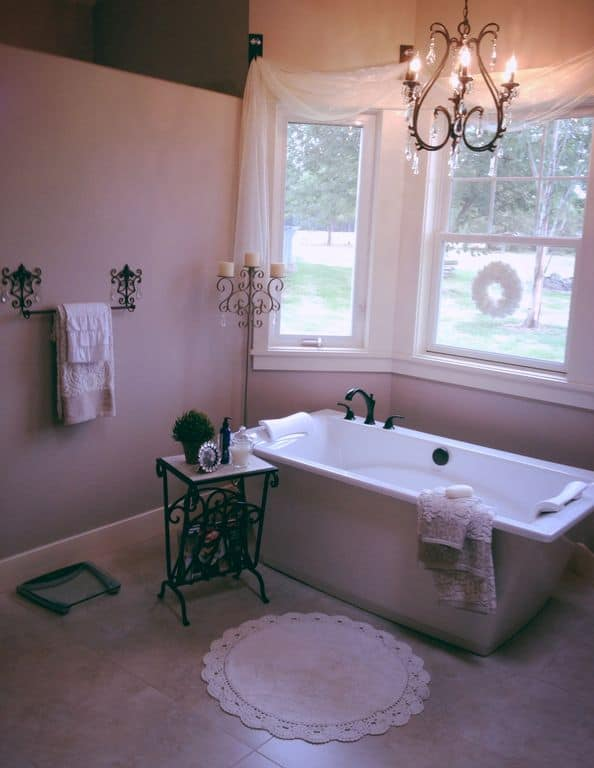 A small bathroom featuring a freestanding tub set on the tiles flooring. The room is surrounded by purple walls.