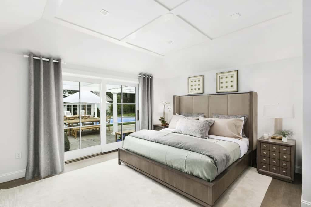 This master bedroom featuring a modish bed setup along with stylish wooden side tables.