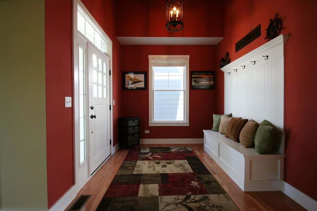 A simple foyer featuring red walls and a tall ceiling, along with a stylish rug.