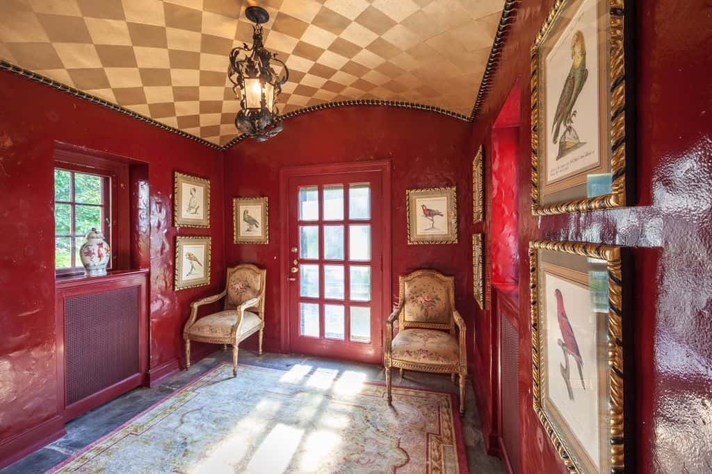 Eclectic style foyer with checker ceiling and red walls, along with two chairs near the doorway and multiple framed wall decors.