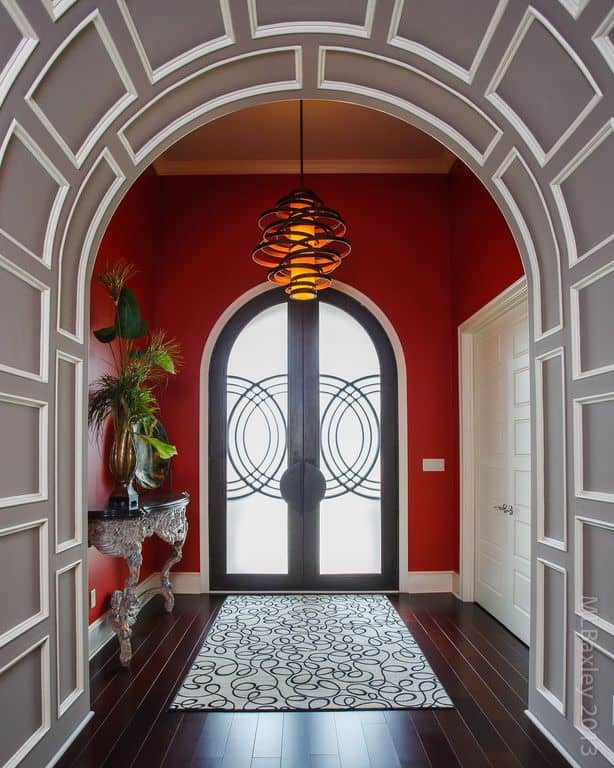 Modern entryway with stylish archway and red walls, along with rich dark hardwood floors.