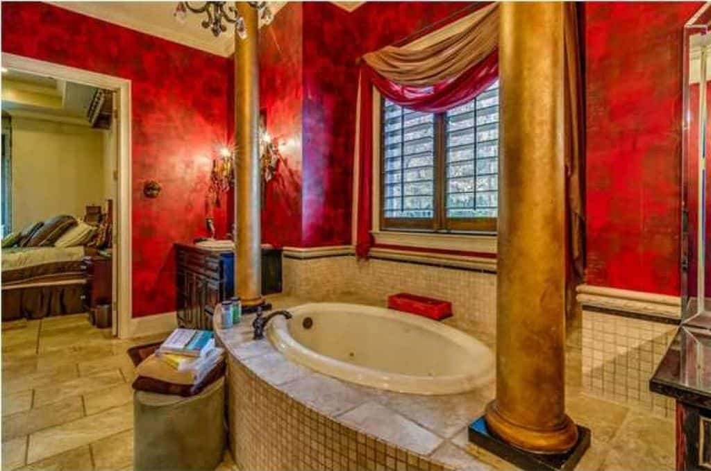 This master bathroom features a Romantic-style drop-in tub surrounded by red walls and is lighted by a small chandelier.