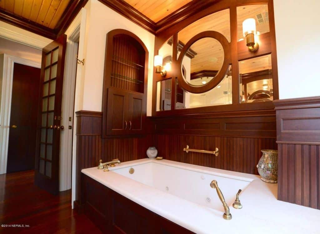 A master bathroom featuring reddish hardwood floors, a drop-in tub with a reddish platform and a wooden regular ceiling.