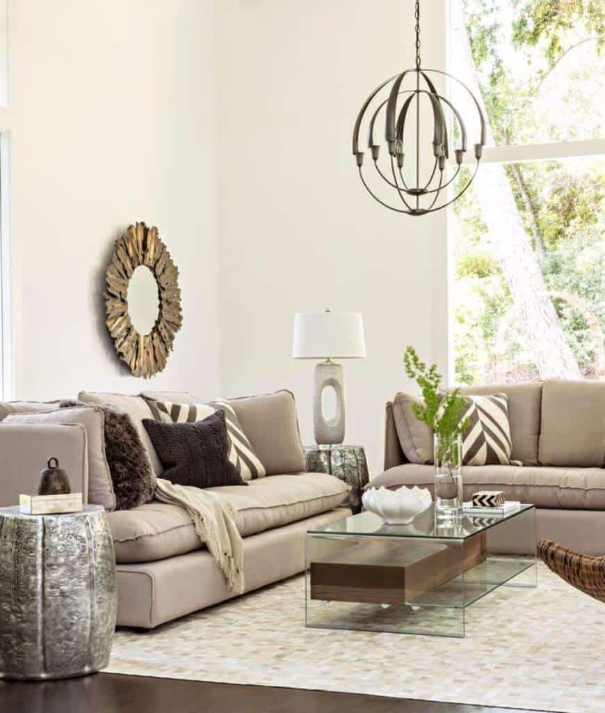 Fresh living room designed with a spherical chandelier and sunburst mirror that hung above the gray sofa filled with various pillows.